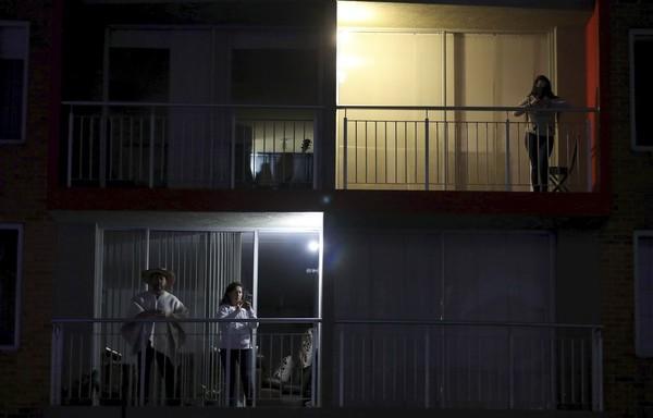 Warga yang ingin menonton film tersebut tidak memerlukan tiket, mereka dapat menontonnya dari balkon tempat tinggalnya tanpa harus keluar rumah. (AP Photo/Fernando Vergara)