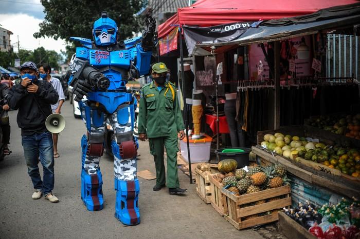 Petugas keamanan yang tergabung dalam Satuan Tugas Anti Nongkrong mengenakan kostum robot saat berpatroli keliling kampung di Sekepanjang, Bandung, Jawa Barat, Senin (4/5/2020). Karang Taruna serta pengurus RW setempat melakukan cara unik dengan berpakaian kostum robot untuk memberikan imbauan kepada warga agar menghindari kerumunan serta tetap berada di rumah guna menekan angka penyebaran COVID-19. ANTARA FOTO/Raisan Al Farisi/wsj.