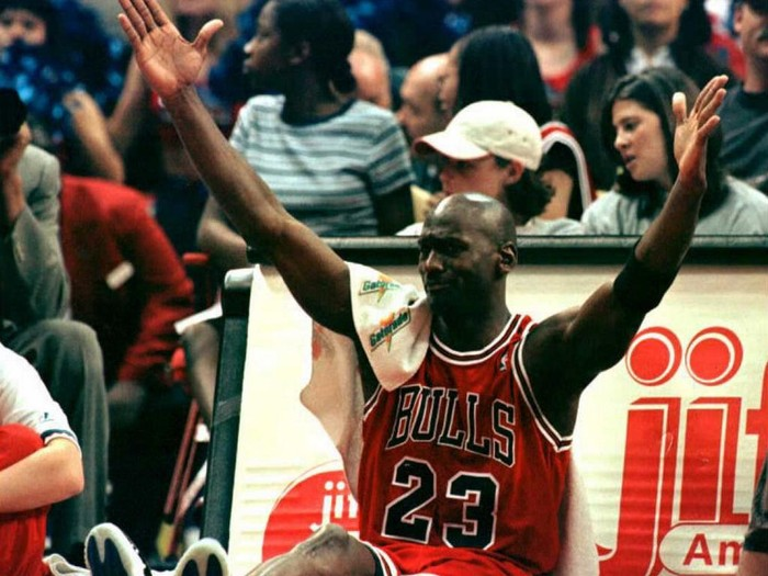 While sitting by the scorers table before returning to play, Michael Jordan of the Chicago Bulls celebrates after a teammate scored a three point shot in the fourth quarter of Chicagos 103-93 win over the Washington Bullets at USAir Arena in Landover, Maryland 21 April. The Bulls ended the regular season with a record of 72-10. AFP PHOTO/Ted MATHIAS (Photo by TED MATHIAS / AFP)
