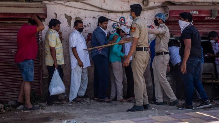 India mulai melonggarkan lockdown. Situasi ini dimanfaatkan warga untuk antre beli miras dengan mengabaikan jaga jarak. Polisi pun memukul warga dengan tongkat.