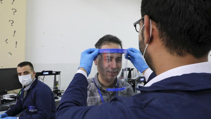 A Palestinian engineer, at the Palestine Polytechnic University in the West Bank town of Hebron, checks the fit of a face-shield that they printed using a 3-D printer on April 21, 2020, as they finalise the design of the shield to help the frontline workers in their effort to combat the spread of the coronavirus (COVID-19). (Photo by HAZEM BADER / AFP)