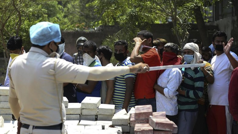 A police personnel gestures to people queueing up to buy alcohol outside a liquor shop after the government eased a nationwide lockdown imposed as a preventive measure against the spread of the COVID-19 coronavirus in New Delhi on May 5, 2020. (Photo by SAJJAD HUSSAIN / AFP)