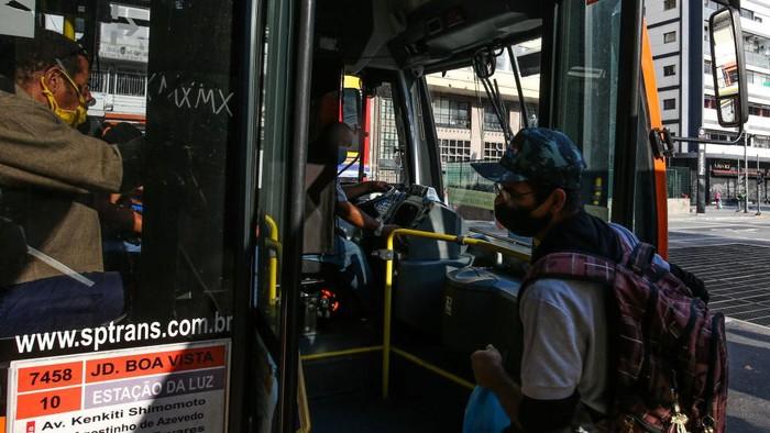 Seorang penumpang dengan mengenakan masker berjalan di stasiun kereta bawah tanah di tengah-tengah pandemi COVID-19 pada 4 Mei 2020 di Sao Paulo, Brasil.