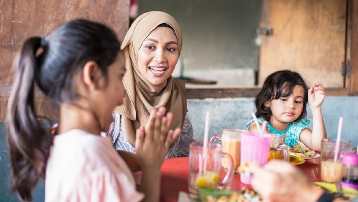 Asian family lunch outdoors, children having fun at table, Father helps feed daughter