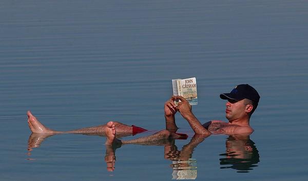 Fakta ini dimanfaatkan oleh wisatawan untuk merasakan sensasi di Laut Mati. Mereka membaca koran sambil mengapung. (Getty Images)