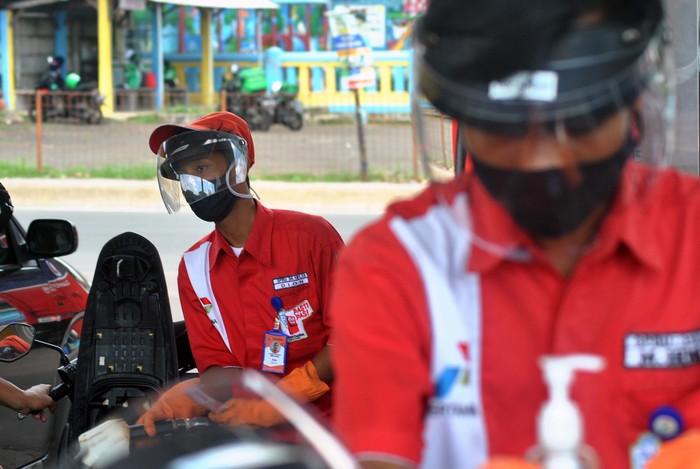 Petugas SPBU menggunakan alat pelindung wajah saat melayani pengendara motor di SPBU 34-16113, Cilendek, Kota Bogor, Jawa Barat, Selasa (5/5/2020). Petugas SPBU yang berhubungan langsung dengan pengendara tersebut menggunakan alat pelindung wajah sebagai upaya untuk melindungi diri, keluarganya maupun orang lain dalam upaya pencegahan penyebaran COVID-19. ANTARA FOTO/Arif Firmansyah/foc.