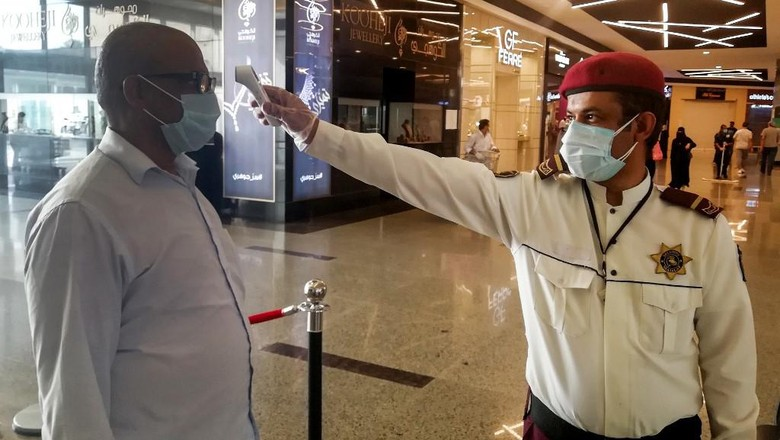 A security guard checks temperature of man arriving at a shopping mall, as a screening precaution against the COVID-19 coronavirus pandemic, in the Saudi capital Riyadh on May 4, 2020, as malls reopen after authorities began a partial lifting of the coronavirus lockdown. (Photo by FAYEZ NURELDINE / AFP)