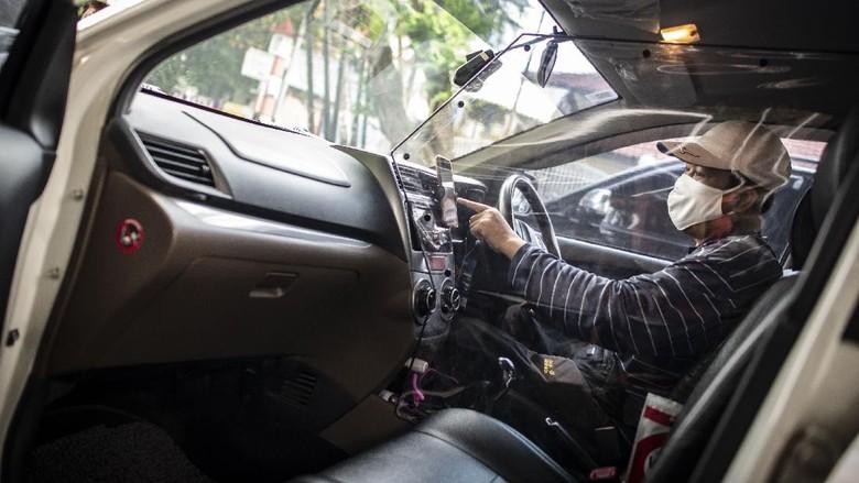 Pengemudi taksi daring, Aris Hardy Halim menunggu calon penumpang di dalam mobilnya yang telah terpasang plastik pembatas di kawasan Bendungan Hilir,  Jakarta, Jumat (8/5/2020). Pemasangan plastik pembatas antara pengemudi dengan penumpang tersebut bertujuan untuk mencegah penyebaran COVID-19 sehingga memberikan kenyamanan dan keamanan kepada pelanggan taksi daring. ANTARA FOTO/Aprillio Akbar/pras.