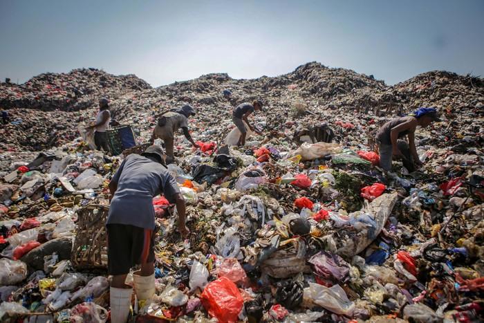 Warga melintas di depan tumpukan sampah di Tempat Pembuangan Akhir (TPA) Rawa Kucing, Kota Tangerang, Banten, Kamis (7/5/2020). Volume sampah Kota Tangerang meningkat dari 1200 ton menjadi 1500 ton perhari atau meningkat 20 persen saat pelaksanaan Pembatasan Sosial Berskala Besar (PSBB). ANTARA FOTO/Fauzan/aww.