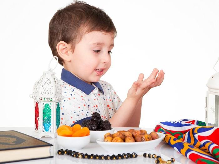 Young Muslim boy praying to Allah while waiting for iftar( breakfast ) in Ramadan