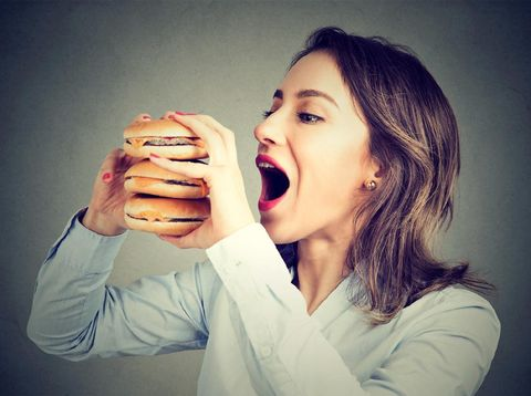 Woman eating craving a tasty double burger