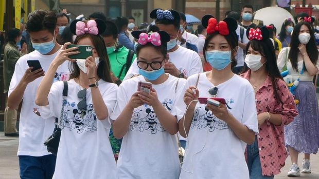 Visitors, wearing face masks, enter the Disneyland theme park in Shanghai as it reopened, Monday, May 11, 2020. Visits will be limited initially and must be booked in advance, and the company said it will increase cleaning and require social distancing in lines for the various attractions.(AP Photo/Sam McNeil)