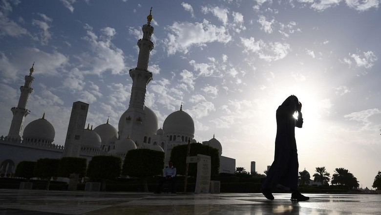 A picture taken on November 6, 2018 shows a visitor in front of the Sheikh Zayed Grand Mosque in the Emirati capital Abu Dhabi. (Photo by GIUSEPPE CACACE / AFP)