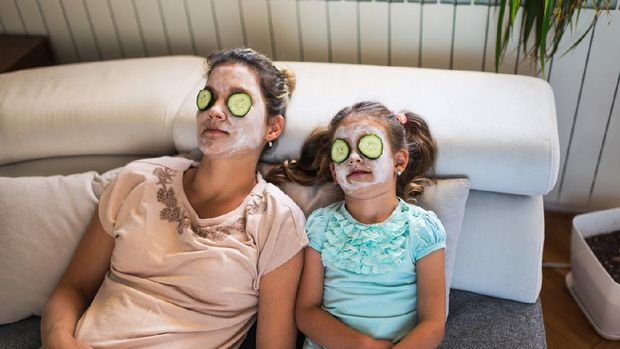 Beautiful mother and daughter with facial mask and slices of cucumber on their eyes enjoying lazy virtual spa day during COVID-19 isolation.