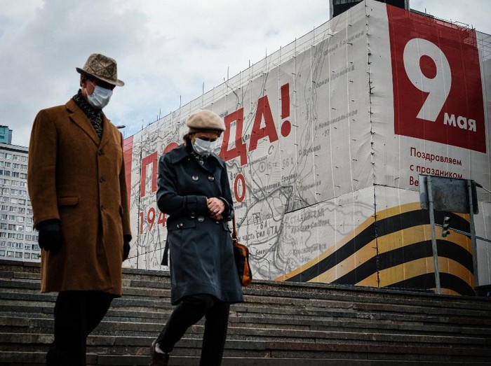 A couple wearing face masks, amid concerns of the COVID-19 coronavirus, walks in front of a huge banner for the upcoming 75th anniversary of the victory over Nazi Germany in World War II that is used to cover a building under renovation in central Moscow on May 7, 2020. (Photo by Dimitar DILKOFF / AFP)