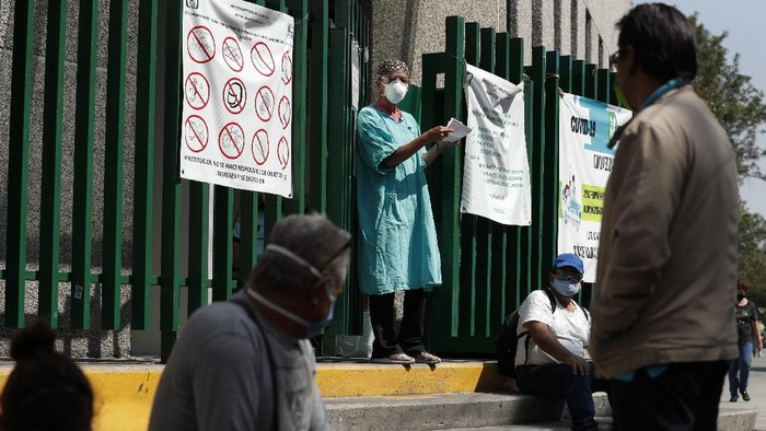 A hospital worker calls out a name from the gate, as relatives of hospitalized patients wait outside in hopes of receiving news of their loved ones, at a public hospital in the Iztapalapa district of Mexico City, Tuesday, May 5, 2020. Iztapalapa has the most confirmed cases of the new coronavirus within Mexicos densely populated capital, itself one of the hardest hit areas of the country with thousands of confirmed cases and around 500 deaths.(AP Photo/Rebecca Blackwell)