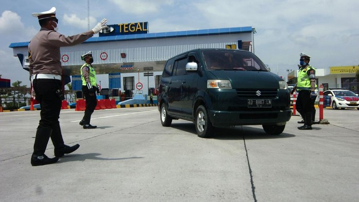 Petugas kepolisian menghentikan kendaraan saat penyekatan di pintu keluar tol Adiwerna, Kabupaten Tegal, Jawa Tengah, Sabtu (25/4/2020). Penyekatan oleh Polres Tegal, PMI dan Dinas Perhubungan Kabupaten Tegal itu dilakukan menyusul adanya larangan mudik oleh Pemerintah guna mencegah penyebaran COVID-19. ANTARA FOTO/Oky Lukmansyah/hp.