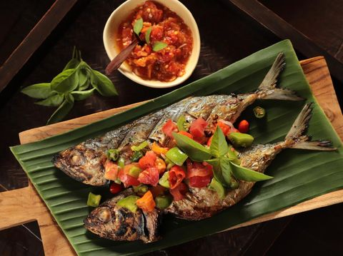 Ikan Tude Bakar Sambal Dabu, a popular Minahasan dish of char-grilled mackerel topped with Dabu-dabu salsa, which is the Minahasan fresh salsa of tomatoes, chili peppers, and shallot. The fish is plated on rectangular wooden board lined with banana leaf. A small bowl of Sambal Rica (Minahasan red chili pepper paste) is served as extra condiment to the grilled fish.