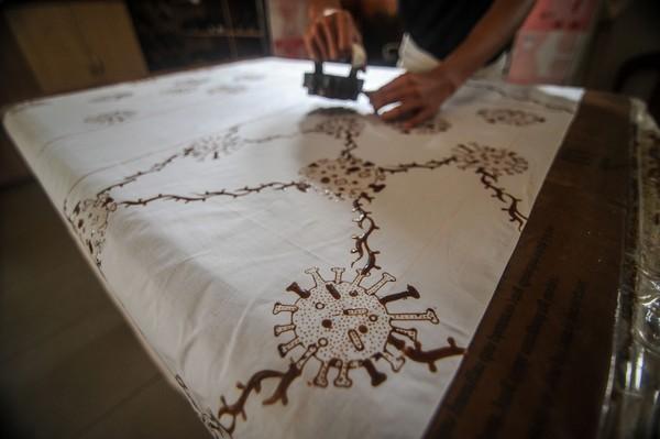 Perajin mencetak motif batik bergambarkan virus Corona pada kain yang akan dijadikan baju di Batik Komar, Bandung, Jawa Barat.