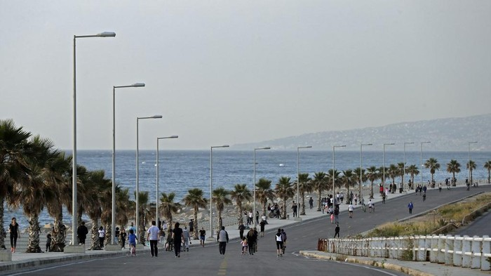 Lebanese people exercise on an empty road by the Dbayeh seaside promenade at the northern entrance of the capital Beirut, after the easing of lockdown measures established to curb the spread of the COVID-19 pandemic, on May 8, 2020. (Photo by JOSEPH EID / AFP)