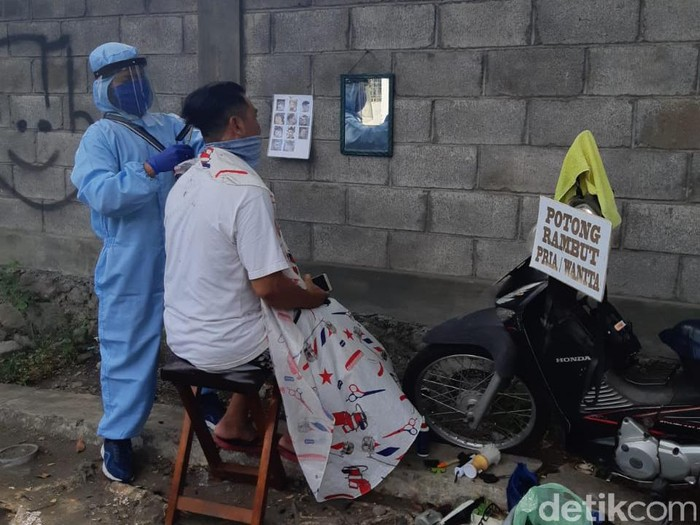 Foto tukang cukur keliling di Surabaya viral di media sosial. Tukang cukur tersebut mencuri perhatian karena menggunakan APD tenaga medis.