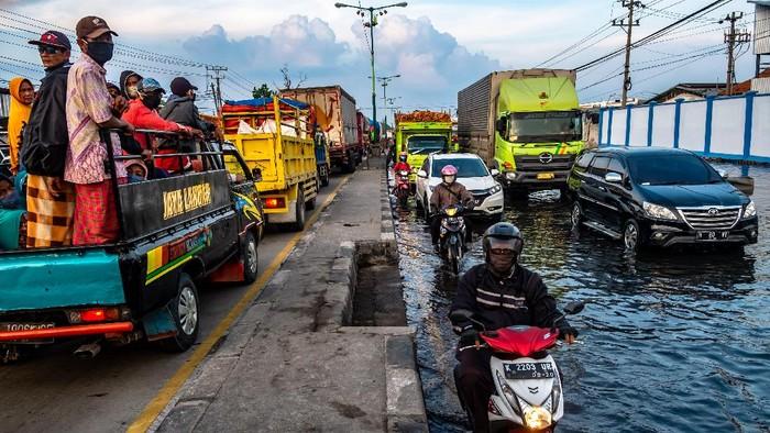 Kendaraan bermotor menembus jalan raya pantura Demak KM 8 ruas Demak-Semarang yang terendam limpasan air laut ke daratan (rob) di Demak, Jawa Tengah, Rabu (13/5/2020). Banjir rob yang melimpas ke jalur utama pantura Demak setinggi sekitar 15-40 sentimeter itu menyebabkan kemacetan lalu lintas sepanjang sekitar 7,5 kilometer dari arah Kabupaten Demak menuju Kota Semarang dan sepanjang sekitar satu kilometer dari arah Kota Semarang menuju Kabupaten Demak. ANTARA FOTO/Aji Styawan/foc.