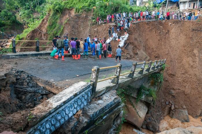 Warga secara swadaya membangun kembali akses jalan di jembatan yang putus di Kampung Cinyiru, Lebak, Banten, Rabu (13/5/2020). Menurut keterangan warga setempat jembatan penghubung antarprovinsi Banten-Jawa Barat tersebut putus akibat hujan dengan intensitas tinggi dan menyebabkan aliran sungai meluap yang terjadi sejak Selasa (12/5) sore hingga malam hari. ANTARA FOTO/Muhammad Bagus Khoirunas/aww.