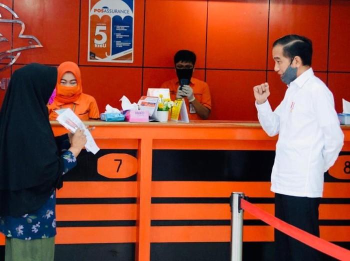 Presiden Joko Widodo (Jokowi) meninjau penyerahan bantuan tunai kepada sejumlah keluarga penerima manfaat yang digelar di Kantor Pos Jalan Ir. H. Juanda, Kota Bogor, pada Rabu, 13 Mei 2020. Bantuan tunai tersebut diberikan kepada masyarakat agar tetap memiliki daya beli di tengah pandemi Covid-19.