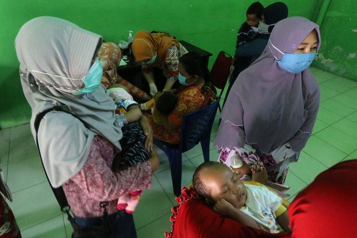 Sejumlah ibu bersama bayinya antre untuk mendapatkan imunisasi di kantor Kelurahan Pesantren, Kota Kediri, Jawa Timur, Kamis (14/5/2020). Pemberian imunisasi yang biasanya dilaksanakan di puskesmas tersebut dialihkan ke kantor kelurahan setempat untuk mengurangi interaksi sosial dan memisahkan anak dari orang sakit guna menghindari penyebaran COVID-19. ANTARA FOTO/Prasetia Fauzani/NZ