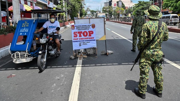 Philippine police man a checkpoint on the border between Quezon city and Manila districts on March 18, 2020, as the government imposed measures to curb the spread of the COVID-19 coronavirus. - Philippine President Rodrigo Duterte ordered about half the countrys population to stay home for the next month in a drastic bid on March 16 to curb the rising number of new coronavirus cases. If fully enforced, the sweeping order would mean most of the 55 million people on the main island of Luzon, which includes the capital Manila, would be housebound. (Photo by Ted ALJIBE / AFP)