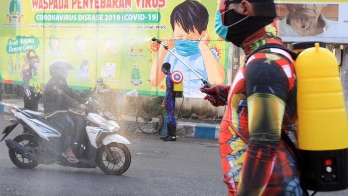 Pengendara melintas di spanduk imbauan terkait bahaya Virus Corona (COVID-19) di Pasuruan, Jawa Timur, Selasa (14/4/2020).  Pemerintah Kota Pasuruan terus melakukan upaya preventif untuk mencegah penyebaran virus corona (COVID-19) dengan memasang sejumlah spanduk di jalan. ANTARA FOTO/Umarul Faruq/hp.