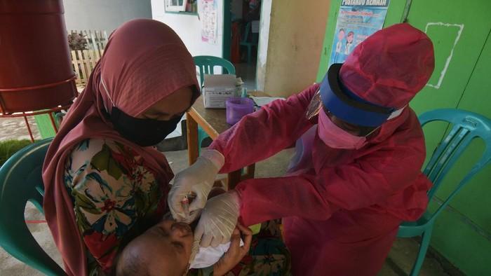Petugas memberikan vaksin kepada salah satu anak saat imunisasi di salah satu posyandu di Palu, Sulawesi Tengah, Rabu (6/5/2020). Meski tengah dilanda pandemi COVID-19, pelaksanaan imunisasi yang bertujuan untuk menjaga kesehatan anak tersebut tetap berjalan, dengan menerapkan jaga jarak (physical distancing), dilaksanakan pada ruang terbuka serta wajib menggunakan masker. ANTARA FOTO/Mohamad Hamzah/aww.