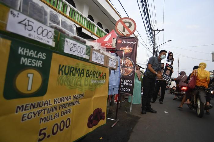 Karyawan salah satu gerai pizza menawarkan produk kepada warga yang melintas di Pondok Betung, Tangerang Selatan, Banten, Rabu (13/5/2020). Ditutupnya sejumlah gerai yang berada di pusat-pusat perbelanjaan imbas dari Pembatasan Sosial Berskala Besar (PSBB), disiasati oleh restoran pizza tersebut dengan melakukan aksi jemput bola ke konsumen sebagai upaya bertahan di tengah pandemi COVID-19. ANTARA FOTO/Puspa Perwitasari/foc.