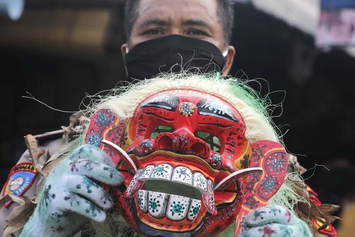 Seorang polisi Bali melakukan hal unik dalam kampanye memakai masker. Dia mendatangai warga dengan memakai topeng tradisional Bali, celuluk. Begini aksinya.