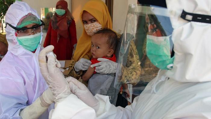 Dua petugas medis dengan alat pelindung diri (APD) dari Puskesmas Babakan bersiap memberikan suntikan imunisasi kepada seorang balita di Posbindu Cempaka 2 Babakan, Tangerang Selatan, Banten, Selasa (12/5/2020). Pelayanan imuniasi tersebut untuk menjaga kesehatan anak walaupun di masa pandemi COVID-19, dengan mengedepankan protokol kesehatan pencegahaan penularaan COVID-19 saat memberikan pelayanan. ANTARA FOTO/Muhammad Iqbal/foc.