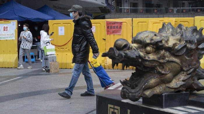 In this photo taken Sunday, April 5, 2020, residents walk near a sealed off neighborhood in Wuhan, central Chinas Hubei province. Authorities in Wuhan, the Chinese city where the coronavirus pandemic first broke out, have reportedly launched a plan to test everyone in the city of 11 million people in the next 10 days. (AP Photo/Ng Han Guan)