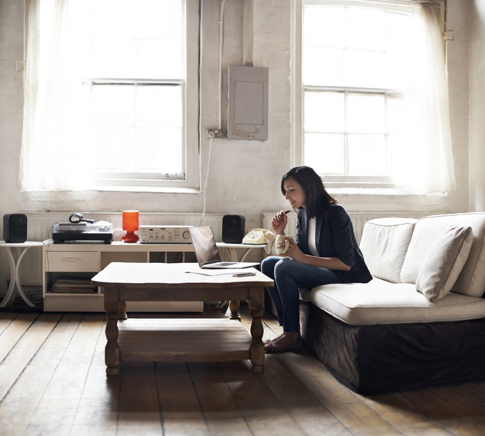 Woman sitting on sofa using laptop in her cozy loft apartment