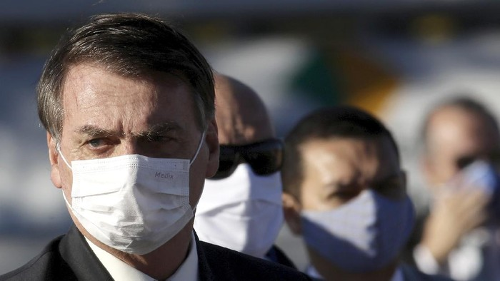 Brazils President Jair Bolsonaro arrives for a flag raising ceremony outside Alvorada palace, the presidential residence in Brasilia, Brazil, Tuesday, May 12, 2020. The morning ceremony flew Brazils flag at half mast to mourn those who have died from the new coronavirus. (AP Photo/Eraldo Peres)