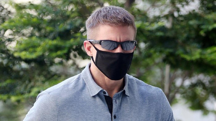CORRECTS SOURCE - In this May 13, 2020, photo, Brian Dugan Yeargan, wearing a face mask and sunglasses, walks outside the Singapore State Court in Singapore. The 44-year-old American pilot has been jailed for four weeks for breaching a quarantine order in Singapore. Local media reported that Brian Dugan Yeargan was sentenced by a court Wednesday, May 13 for leaving his hotel room for three hours to buy masks and a thermometer.  (The Straits Times via AP)