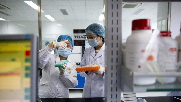 Employees work in a research and development lab of Beijing Applied Biological Technologies, a firm which is developing COVID-19 molecular diagnostic test kits, during a government organized tour for journalists in Beijing, Thursday, May 14, 2020. China reported three new coronavirus cases Thursday while moving to reopen for business and schools. (AP Photo/Mark Schiefelbein)