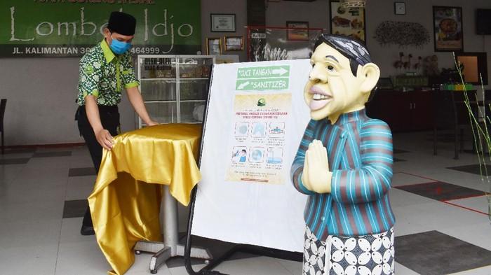 Karyawan bekerja di sebuah rumah makan untuk persiapan menerima pengunjung di Kota Madiun, Jawa Timur, Jumat (15/5/2020). Pemkot Madiun mulai Jumat (15/5) membolehkan rumah makan melayani pengunjung yang menginginkan makan di tempat dengan tetap menerapkan protokol kesehatan pencegahan penyebaran COVID-19 setelah sebelumnya selama sekitar dua bulan hanya melayani pembelian dengan cara dibungkus dan dibawa pulang. ANTARA FOTO/Siswowidodo/wsj.