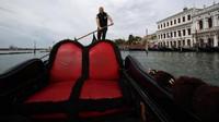 Pemilik perahu gondola sewaan, Andrea Balbi mendorong perahunya di Grand Canal, Venesia, (13/5/2020). Statistik ekonomi Venesia mencatat pemasukan dari industri wisata mencapai 3 miliar euro per tahun. Namun angka itu sulit terealisasi tahun ini karena pandemi global.