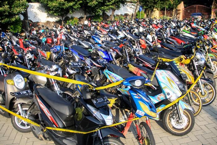 Ratusan kendaraan bermotor milik warga yang terjaring razia terparkir di halaman Polresta Sidoarjo, Jawa Timur, Minggu (17/5/2020). Kepolisian Resor Kota Sidoarjo Jawa Timur berhasil mengamankan 224 kendaraan bermotor yang diduga digunakan saat balap liar motor di akses jalan exit tol porong saat pemberlakuan pembatasan sosial berskala besar (PSBB) dan melakukan pembinaan terhadap 500 pemuda yang turut terjaring dalam razia itu agar tidak mengulangi perbuatannya. ANTARA FOTO/Umarul Faruq/foc.