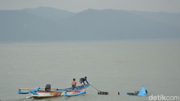 Nelayan berusaha mengevakuasi perahunya yang karam akibat badai yang melanda pantai timur Pangandaran.
