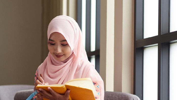 Muslim concept. Young muslim woman writing notebook paper, relaxing and enjoying her book.