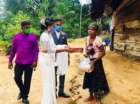 Pasangan pengantin Darshana dan Pawani membagikan makanan kepada sesama.