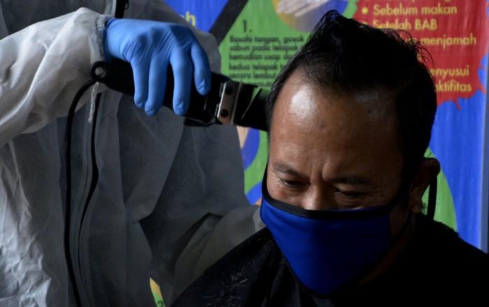 Mahasiswa Fakultas Teknologi Industri Universitas Muslim Indonesia (FTI UMI)  Makassar memangkas rambut seorang dokter sambil menggunakan Alat Pelindung Diri (APD) di Makassar, Sulawesi Selatan, Minggu (17/5/2020). Kegiatan itu diberikan kepada sejumlah dokter yang telah bertugas menangani pasien yang terjangkit virus COVID-19 selama dua bulan di rumah sakit. ANTARA FOTO/Abriawan Abhe/aww.