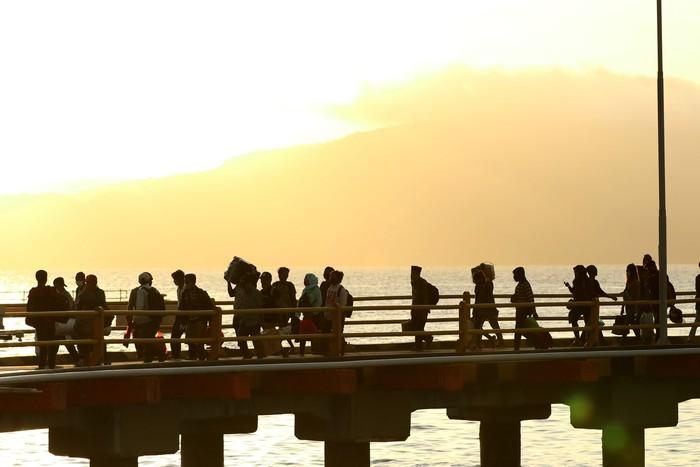 Petugas kesehatan memeriksa suhu tubuh para pemudik usai turun dari kapal di Pelabuhan Ketapang, Banyuwangi, Jawa Timur, Senin (18/5/2020). Pada H-6 arus mudik Idul Fitri dari Pulau Bali dengan tujuan Pulau Jawa di Pelabuhan Ketapang terpantau ramai penumpang pejalan kaki. ANTARA FOTO/Budi Candra Setya/wsj.