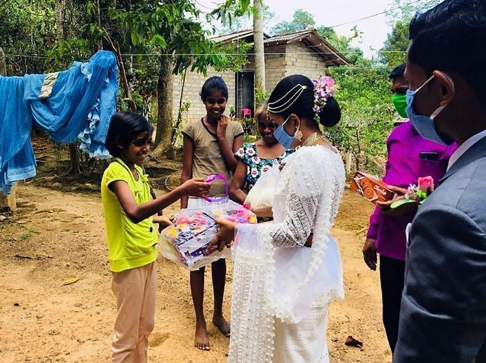 In this April 27, 2020, photo, Pawani Rasanga hands a care package to a child in the small town of Malimbada, about 160 kilometers (99 miles) south of the capital Colombo. Rasanga and her groom cancelled a wedding party and instead, shared their wedding day with some of their neediest neighbors who have been economically hit due to the lock down following the new Coronavirus. (Darshana Kumara Wijenarayana via AP)