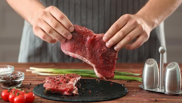 Man preparing meat in kitchen
